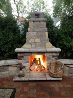Outdoor living spaces with fireplace by Fredrickson Lawn and Landscape